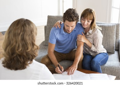 Young owners couple meeting realtor for apartment investment. Signing a contract