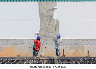 Young painter with blue cap and gloves painting a wall with paint roller; copy space