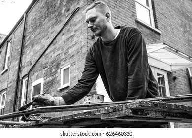 Young painter decorator metalworker painting railings with black paint on workbench of small family business in grey scale