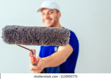 Young painter holding paint roller in front of the wall