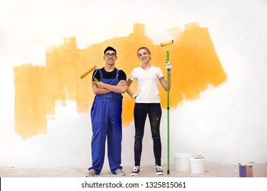 Young painters with rollers indoors