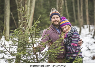 Young pair with a christmas tree in the forest