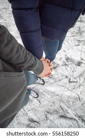 Young pair holding their hand, ice skating on pond