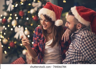 Young pair in love at Christmas night looking at cell phone together