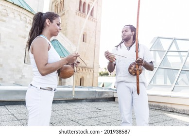 Young pair partners capoeira, berimbau musical instrument in their hands