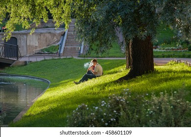 Young pair resting in a park under the tree