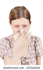 Young pale girl having a cold sneezing and whipping nose with paper tissue