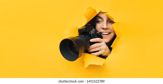 A young paparazzi girl holds a reflex camera and looks through a torn hole in yellow paper. The concept of smile and laughter from what he saw. Copy space.