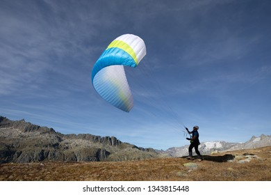 Young paraglider pilot exercises with his paraglider pulling up in the wind, the so-called ground handling. Near Grimsel in the Swiss Alps
