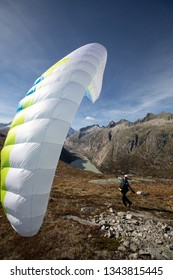 Young paraglider pilot uses his paraglider to play with the wind in the Swiss Alps, the so-called ground handling