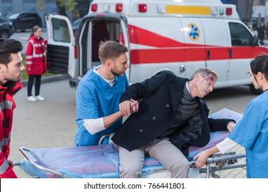 young paramedics helping injured man lie down on ambulance stretcher
