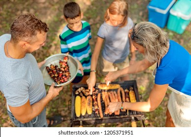 Young parents with children enjoy  barbecue outside
