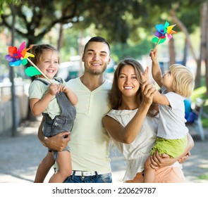 Young parents with children playing windmills in park on vacation day