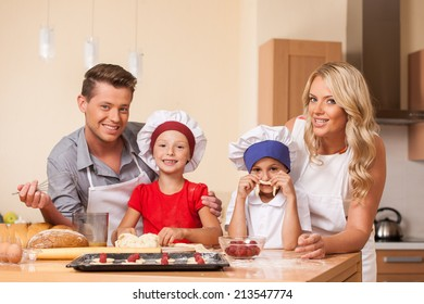 Young parents cooking together with children. boy and girl helping with food at kitchen