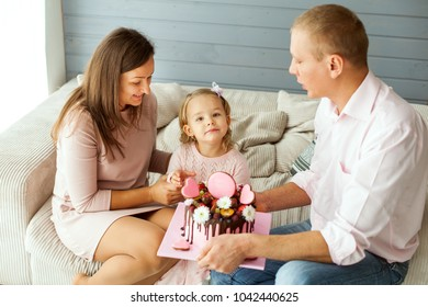 Young parents with a daughter. Dad is holding a birthday cake