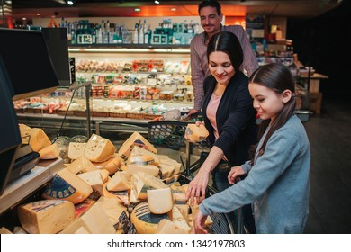 Young parents and daughter in grocery store. Mother help daughter to pick up cheese. Father stand behind and look at it. Family shopping.