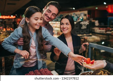 Young parents and daughter in grocery store. Little girl get tasty cake. She reach out with hand and smile. Happy parents stand beside. Father hold daughter.