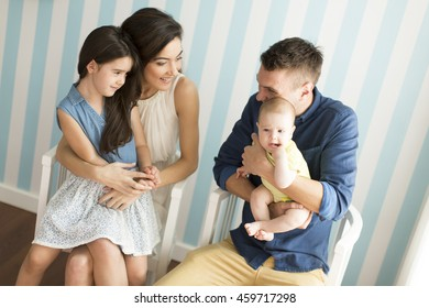 Young parents with daughters in the room