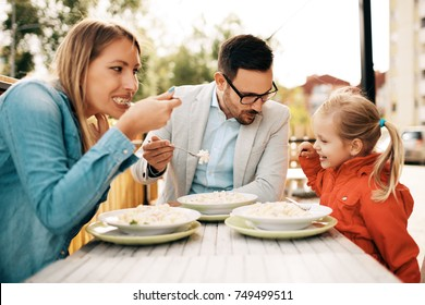 Young parents dining in a restaurant with four years old adorable girl.
