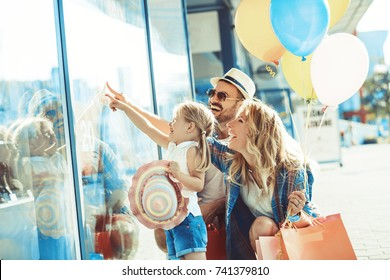Young parents with four years old daughter enjoying shopping.