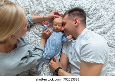 Young parents giving lots of attention to their baby. They are all sitting on a bed at home. top view