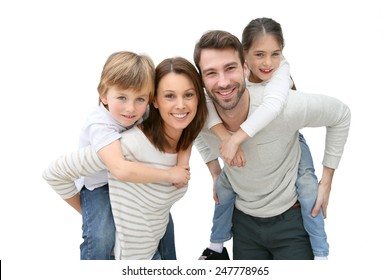 Young parents giving piggyback ride to kids