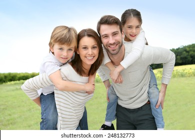 jovem pais dando piggyback passeio para crianças