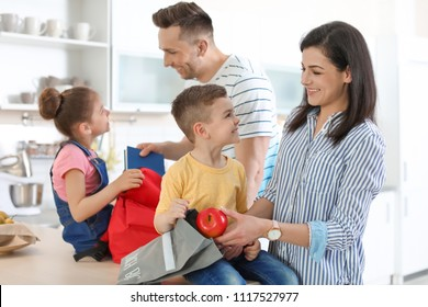 Young parents helping their little children get ready for school at home