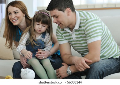 young parents at home with beautiful child make savings and put coins money in piggy bank