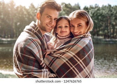 Young parents hugg their little daughter in autumn forest near the lake.