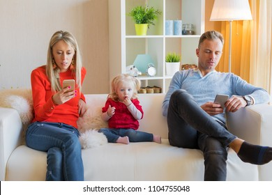 Young parents ignore their kid and looking at their mobile phones