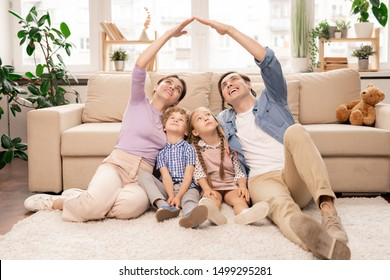 Young parents keeping their hands close forming roof over their two little kids while sitting on the floor of living-room