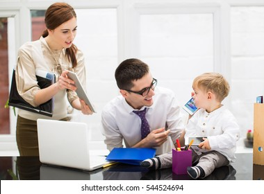Young parents with little boy working In office