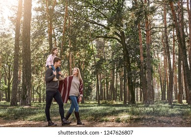 Young parents with little daughter in autumn forest. Side view