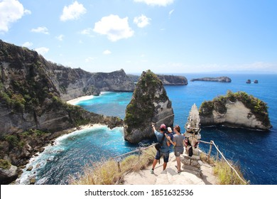Young parents and little kid enjoying the views in Thousand Islands Viewpoint, on of the most amazing spots in Nusa Penida Island, Indonesia, Bali.