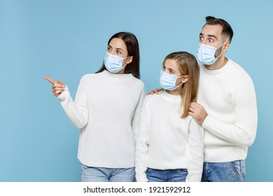 Young parents mom dad with child kid daughter teen girl in sweaters sterile face mask safe from coronavirus virus covid-19 pointing finger aside isolated on blue background. Family parenthood concept