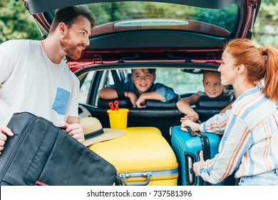 young parents packing luggage in trunk of car with kids on backseats