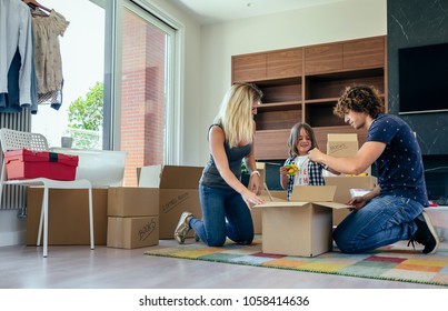 Young parents preparing moving toy box with their little son