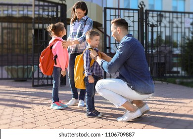 Young parents saying goodbye to their little children near school