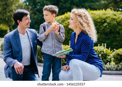 Young parents saying goodbye to their little child near school outdoor. Father, mother and little pupil son having new stage in life.