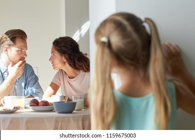 Young parents sharing secreta by breakfast while their little daughter standing by kitchen door and eavesdropping