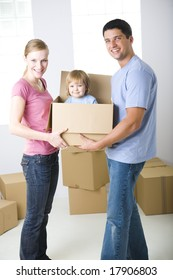 Young parents standing between cardboard boxes. They're holding one box with their daughter. They're looking at camera. Front view.