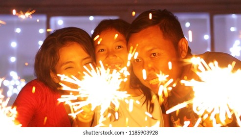 Young parents and their daughter look happy while playing with fireworks at Christmas time