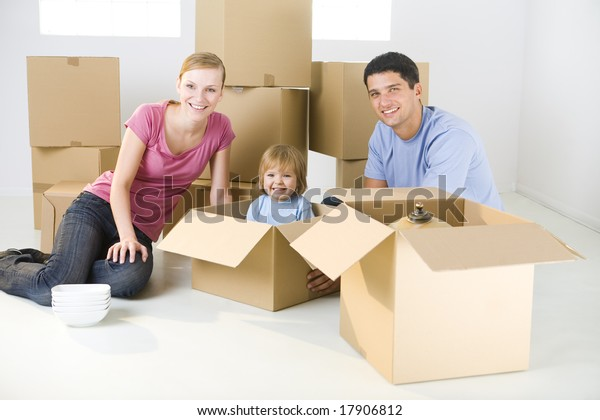 Young parents and their daughter sitting beside cardboard boxes. Young girl sitting in box. They're smiling and looking at camera.