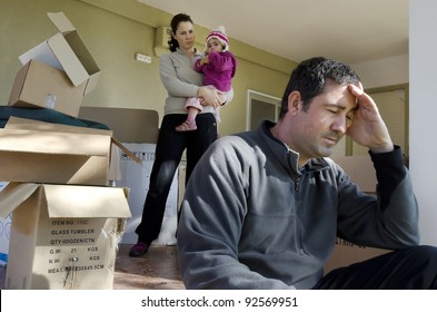 Young parents and their daughter stand beside cardboard boxes outside their home. Concept photo of  divorce, homelessness, eviction, unemployment, financial, marriage, family problems, family issues.