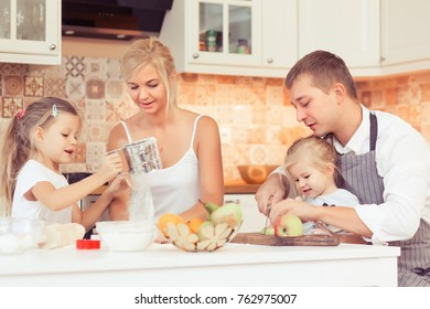 Young parents and their two beautiful and cute children girls cooking and eating breakfast ot lunch at kitchen table at home