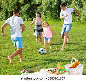 Young parents with theirs children having fun together outdoors, playing football on green grass