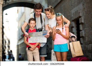 Young parents with two kids traveling together using paper map and phone