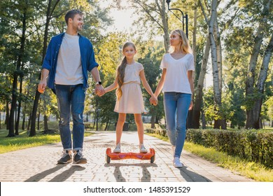 Young parents walking in park with their cute little girl riding hoveboard