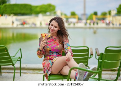 Young Parisian woman in the Tuileries garden, sitting on a chair and eating ice cream